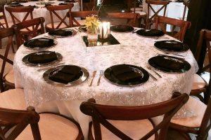 Mesa redonda banquetera de 1.50 metros de diámetro con mantel blanco y cubremantel de lentejuelas plateado. Capacidad hasta para 10 personas, incluye molletón. (Sillas son por separado)